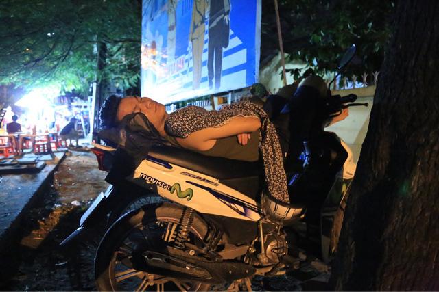 Sau nhiều giờ chờ đợi, phụ huynh này chợp mắt trên yên xe máy.