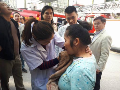 Nhân viên y tế chăm sócngười dân được cảnh sát giải cứu từ vị trí phát hoả. Ảnh: Quang Chiến