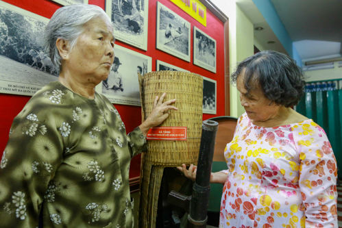 Các cô nữ giao liên góp phần vận chuyển vũ khí từ vùng ven vào các hầm bí mật nội thành Sài Gòn, bên cạnh hiện vật được phục dựng. Ảnh: Thành Nguyễn.